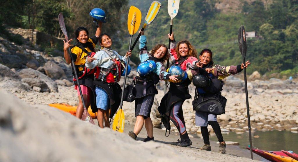 Kvinnliga forsguider i Nepal poserar med sina paddlar på en strand