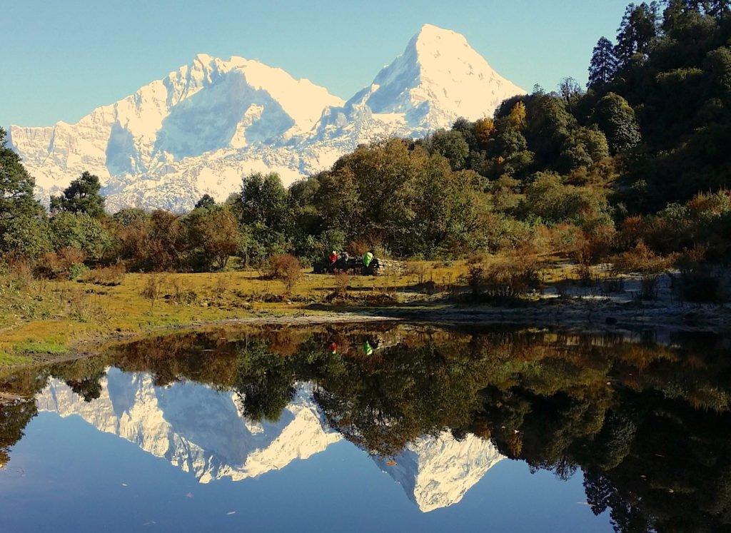 Ekovandring i Nepal. sagolika vyer av berg reflekteras i sjö