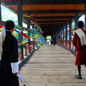 Vi går över en vacker träbro i Paro, Bhutan