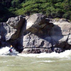 Forspaddlingsresa Nepal, forspaddlare paddlar förbi en stor klippa