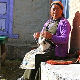 En Sherpakvinna betraktar vandrare på väg till Everest Base Camp