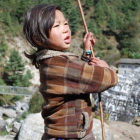 Ett barn leker intill stigen till Everest Base Camp
