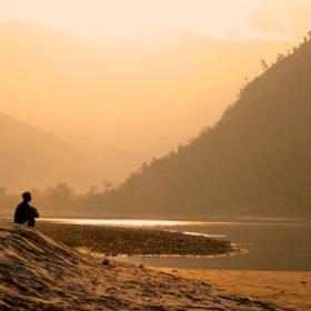 Forspaddling Nepal, en resenär njuter av lugnet på en sandstrand
