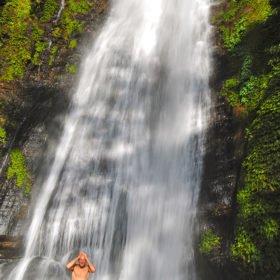 Forspaddling Nepal. En paddlare tvättar sig i ett vattenfall vid floden Sun Kosi