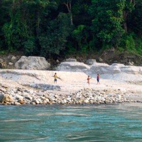 Forspaddling Nepal, nepelesiska barn på en strand vid floden