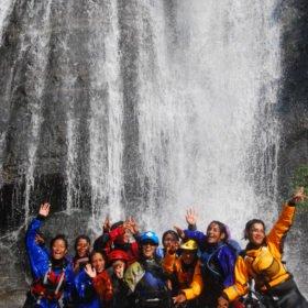 Glada paddeltjejer i ett vattenfall