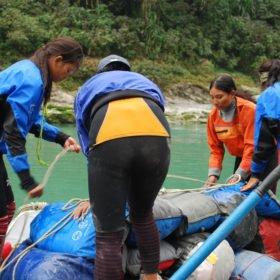 Kvinnliga guider lastar utrustning på en gummiflotte