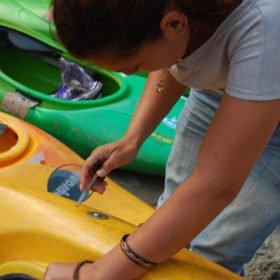 En kvinna lagar en kajak