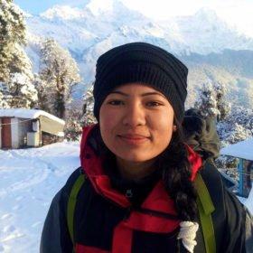 Ung kvinnlig leende guide i ett snötäckt landskap