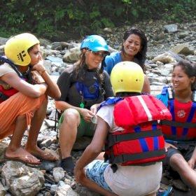 Några nepalesiska flickor i flytvästar lyssnar på sin guide, Inka Gurung