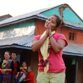 Kvinnlig guide hälsar i en nepalesisk by
