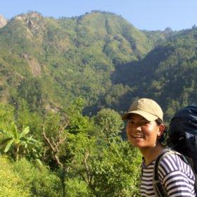 Kamala Magar, en kvinnlig vandringsguide med gröna berg i bakgrunden