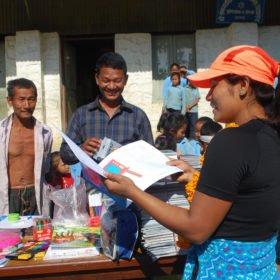 Kvinnlig guide delar ut böcker vid en skola i Nepal