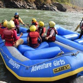 Barn sitter i en gummiflotte, snart klara för avfärd ner genom forsarna med kvinnlig guide