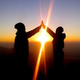 Två tjejer gör en high five framför solnedgången i Nepal