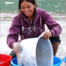 Kvinna diskar en kastrull vid floden