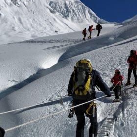 Island Peak. Klättrare går över en stege.