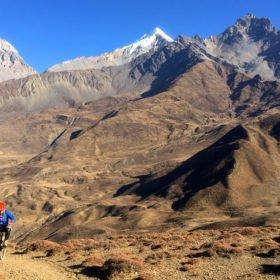 mountainbike-cyklist kommer nerför en stig i ett spektakulärt bergslandskap