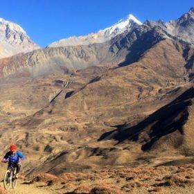 MTB Nepal, en mountainbike-cyklist kommer nerför en stig i ett spektakulärt bergslandskap