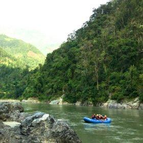 Resa Tibet och Nepal, en grupp flyter fram på en grön flod i en rafting-båt