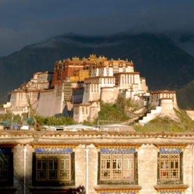 Rundresa Tibet, Potalapalatset. Solen skiner men mörka moln hänger över berget bakom