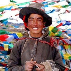Resa Tibet & Nepal, tibetan bland färgglada böneflaggor på ett bergspass i Tibet