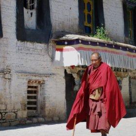 Resa Tibet & Nepal, en äldre munk med röda enkla kläder och en käpp promenerar utanför ett kloster