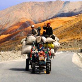 Resa Tibet och Nepal, några tibetaner åker på en liten traktor med enorm last