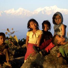 Rundresa Nepal. Barn njuter av solen framför bergen.