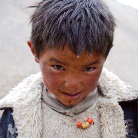 Rundresa Tibet. Tibetansk pojke ler mot kameran.