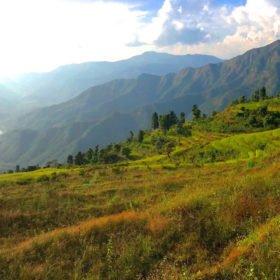 Rundresa Tibet, ett grönt kuperat landskap i Nepal med risterasser