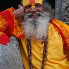Rundresa Tibet. Hinduskt sadhu, i gul/orangea kläder och matchande smink i pannan