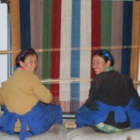 Rundresa Tibet. Kvinnor väver en färgglad tibetansk matta för hand.