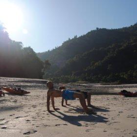 Forspaddlingskurs Nepal. Paddlare yogar på en sandstrand.