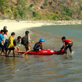 Forspaddlingskurs Nepal, en kvinnlig paddlare får hjälp av en grupp barn att komma i vattnet