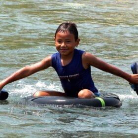 Forspaddlingskurs Nepal. En pojke paddlar med hjälp av en traktorslang och sandaler..