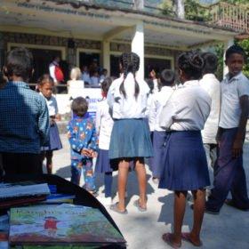 Tjejresa Nepal, skolbarn framför en skolbyggnad samt skolböcker i en väska