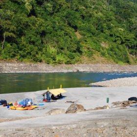 Tjejresa Nepal, kajaker och vindskydd på en strand vid en flod