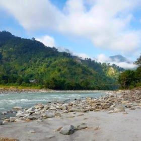 Tjejresa Nepal, forsande flod, sandstrand och gröna kullar