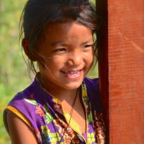 Tjejresa Nepal, en glad flicka betraktar passerande turister