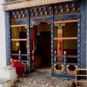 Bhutanresa, en munk i en färgglad dzong