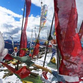 Bhutanresa, färgglada flaggor på ett snötäckt bergspass