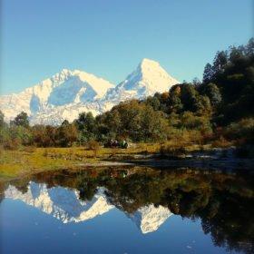 Ekovandring Nepal, snötäckta berg speglar sig i en sjö