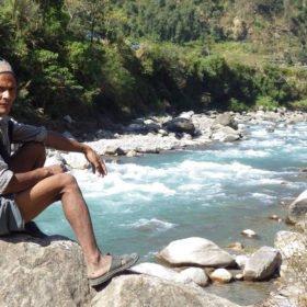 Paddlingsresa Nepal, en nepalesisk man sitter vid floden