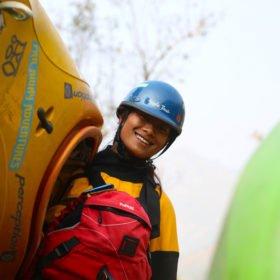 Paddlingsresa Nepal, en kvinnlig forspaddlingsguide med kajak på axeln.