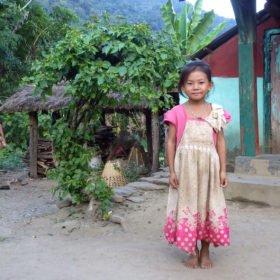 Paddlingsresa, en flicka står leende utanför sitt hus i en by i Nepal