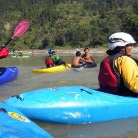 Barn leker i floden med kajakpaddlarna