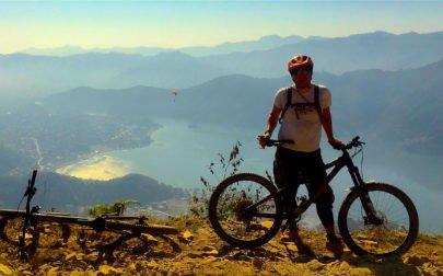 En cyklist med sin mountainbike med vacker utsikt över sjön i Pokhara