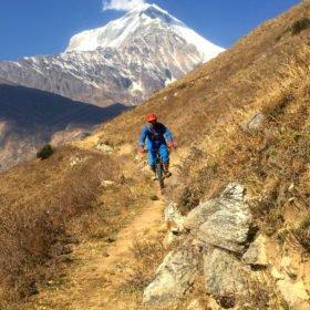 MTB-cyklist på en stig med berg i bakgrunden
