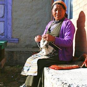 En Sherpakvinna sitter och stickar på stigen mot Everest Basecamp